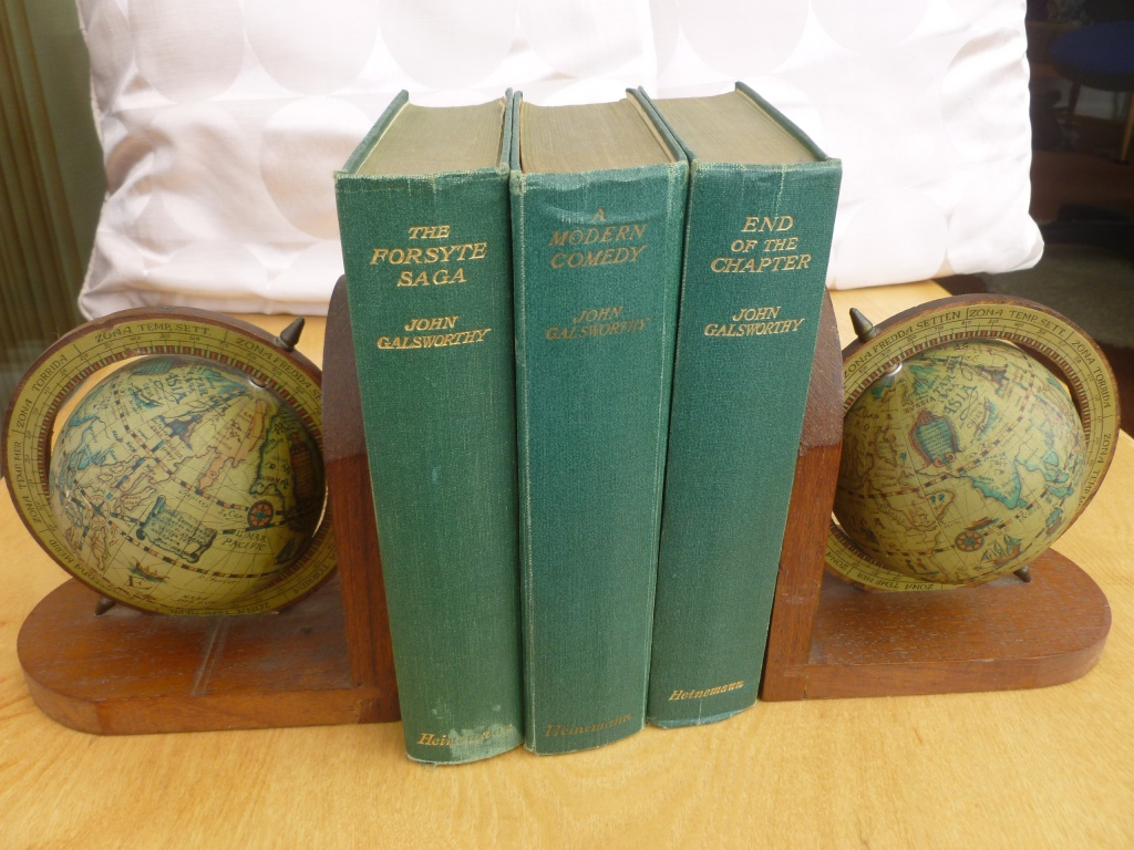 Three green volumes with gold lettering supported by bookends with globes depicting old maps of earth